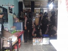 PASRAH: Petugas dari peleton Dalmas Sabhara Polresta Solo mengamankan puluhan liter miras dari salah satu penjual di gandekan Jebres, Rabu (17/1)