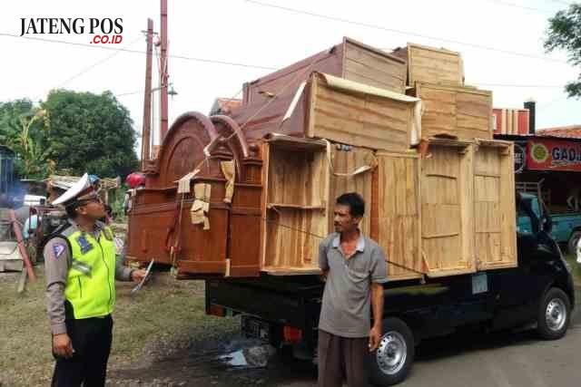 HENTIKAN TRUK: Kanit Patroli Ipda Andi Susanto menghentikan mobil bak terbuka yang kelebihan membawa barang, kemarin.