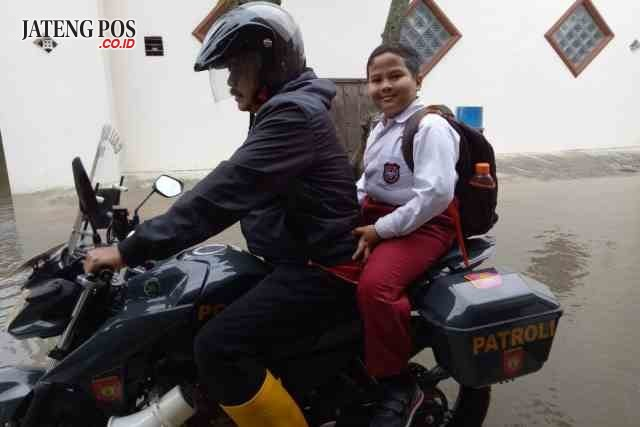 ANTAR – Kapolsek Kompol Agus Riyanto mengantar pelajar SD. (didik teguh r)