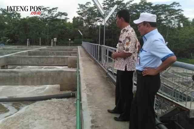 ATASI LIMBAH RUM : Praktisi pertanian Heri Sulistyo (baju batik) sedang melakukan uji coba penanganan limbah PT RUM didampingi Haryo, salah satu direksi PT RUM.