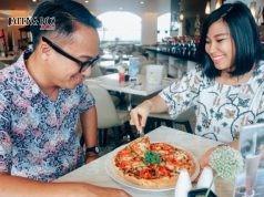 Monica, Public Relation Aston Hotel Semarang tengah melayani tamu yang sedang menikmati Pizza Daging Rendang sebagai menu utama promo Bulan Januari