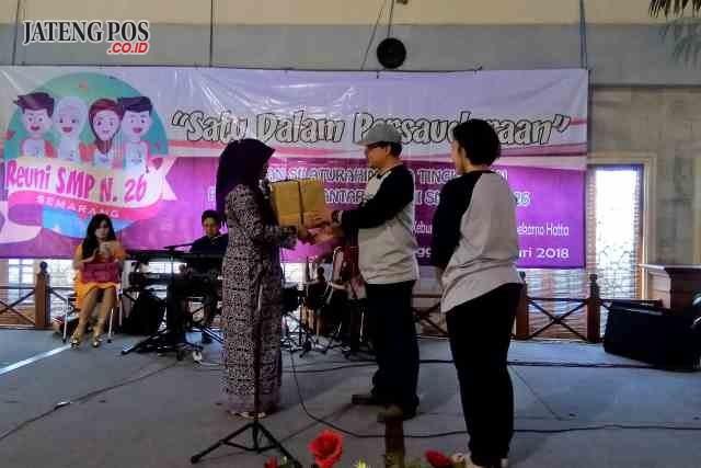 DISERAHKAN : Suprapti, salah satu guru SMP 26 Semarang saat menerima kenangan dari para alumni SMP 26 Semarang angkatan 89-90. Adhi/jateng pos
