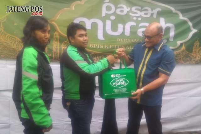 SOSIAL : Kepala Kantor BPJS Ketenagakerjaan Cabang Solo, Suwilwan Rachmat menyerahkan paket sembako dalam Pasar Murah yang dikhususkan bagi peserta BPU driver online dan PKL. (Wijayanti/Jateng Pos)