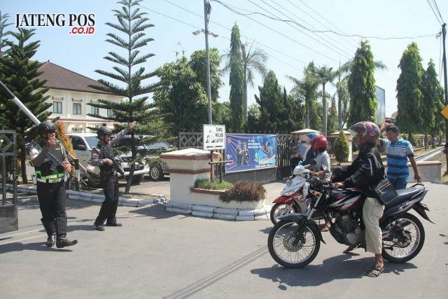 LARAS PANJANG: Pengunjung polres klaten diperiksa oleh anggota bersenjata laras panjang. Foto: cahya indrawan/jatengpos