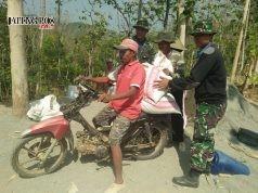 Para prajurit dan warga terpaksa angkut material tanpa alat bantu karena medan yang sulit dijangkau dengan kendaraan. Foto ARI SUSANTO/JATENG POS