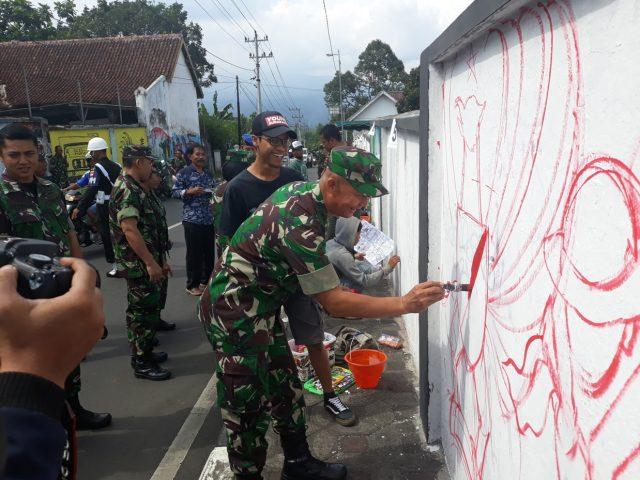 CINTA SENI : Kasrem Letkol ( Inf) Hari Santoso saat menorehkan kuas ke tembok mengawali lomba lukis mural dalam rangka Hari Juang Kartika. ( foto : dekan bawono/ jateng pos).