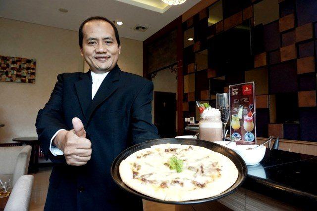 MENU SPESIAL : Muhamad Noor Cholis GM Noorman Hotel Semarang tengah menunjukan menu baru Pizza Rendang. Foto : PRAST WD/JATENG POS.