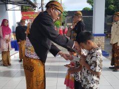 Direktur utama PD BPR BKK Wonogiri Sucipto menyerahkan tabungan simpel ayah saat upacara HUT Merger ke 13, Jumat (18/1/2019). Foto: ade ujianingsih/jatengpos