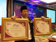 PENGHARGAAN : Henry Indraguna saat menerima dua penghargaan Anugerah Pers 2019 dari PWI Solo di Hotel Lorin Solo, Jumat (15/3) malam.