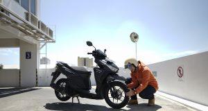 #Cari_Aman: Seorang pengendara motor yang sedang mengecek tekanan ban sebelum berkendara.