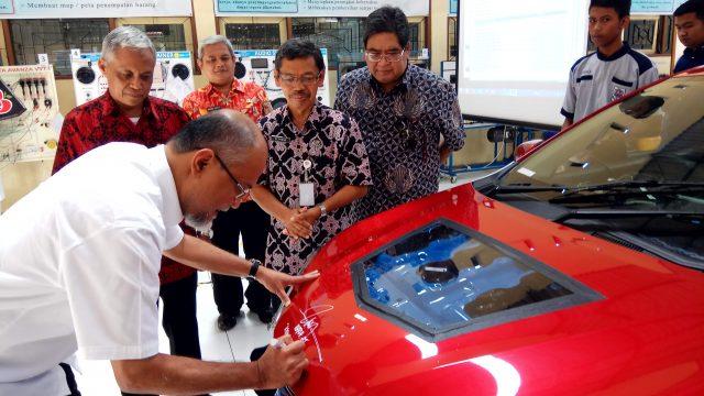 BERI BANTUAN : Presiden Direktur PT Toyota Motor Manufacturing Indonesia, Ir Warih Andang Tjahjono saat membubuhkan tanda tangan pada mobil bantuan untuk pendidikan di SMK 1 Jambu.