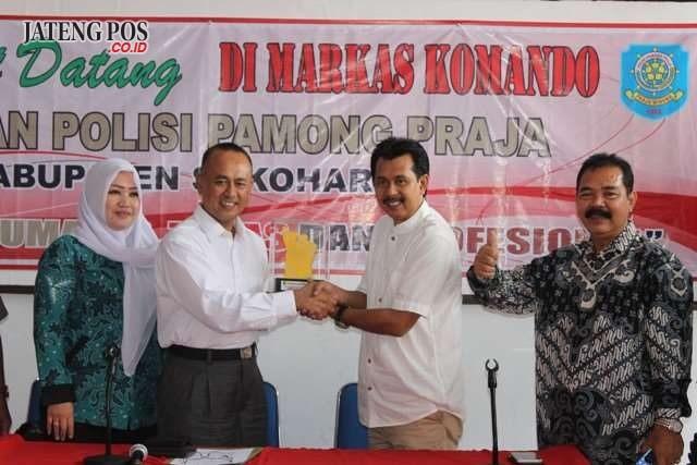 TERIMA PLAKAT : Anggota Komisi A Sriyanto Saputro menerima plakat dari Satpol PP Sukoharjo dalam kunjungan kerja pada Senin (21/5).