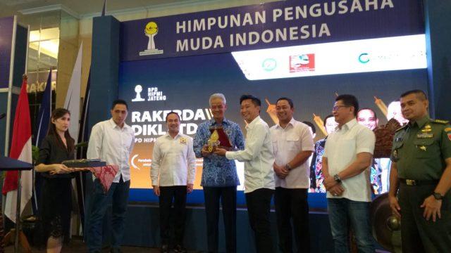 RAKERDA HIPMI - Ketua Umum BPD Hipmi Jateng Billy Dahlan memberikan cinderamata kepada Gubernur Jawa Tengah, Ganjar Pranowo, dalam acara Rakerda 3 dan Diklatda 2 BPD Hipmi Jateng di Hotel Dafam Semarang, Senin (17/6).