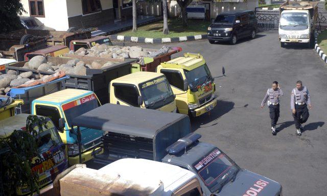 ILEGAL:Polisi mengecek barang bukti truk sitaan di Mapolres Pekalongan, Jawa Tengah, Kamis (6/2/2020). Polres Pekalongan mengamankan barang bukti 13 truk dan 5 ekskavator hasil pengungkapan tindak pidana usaha pertambangan galian batuan tanpa izin (ilegal) di wilayah hukum Polres Pekalongan yang dengan ancaman hukuman 10 tahun penjara dan denda Rp10 miliar. ANTARA FOTO/Harviyan Perdana Putra/aww.